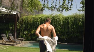 Man takes shirt off and going to the swimming pool, steadycam shot, slow motion
