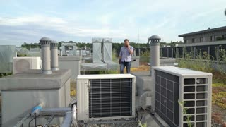 Man talking on cellphone and walking on the roof while checking air condition, s