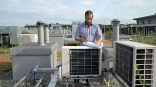 Man talking on cellphone while standing on the roof and working on air condition