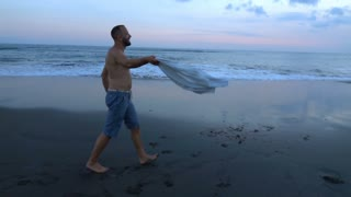 Man walking on the sandy beach and holding shirt, slow motion shot at 240fps, st