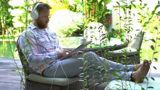 Man wearing headphones and having a videocall on tablet