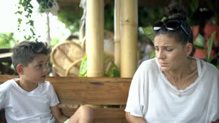 Mother having a quarrel with her son in the tropical cafe, steadycam shot