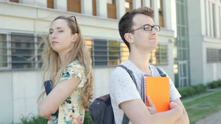 Pair of students standing back to each other and look offended, steadycam shot