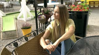 Pretty blonde girl in yellow jacket and ripped jeans sitting in the outdoor cafe