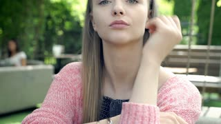Pretty, blonde girl sitting outdoors and doing serious look to the camera, stead