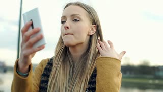 Pretty, blonde girl using smartphone as a mirror while checking her appearance