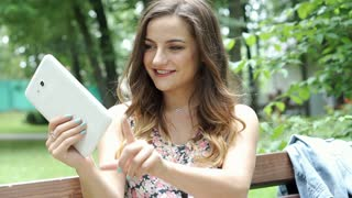 Pretty brunette in floral shirt doing selfies on tablet in the park, steadycam s