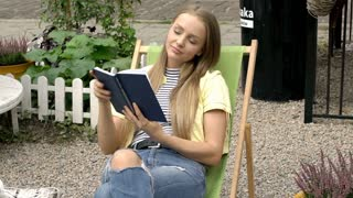 Pretty girl answers cellphone while reading book on sunbed