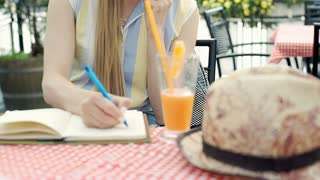 Pretty girl doing notes while speaking on cellphone in the cafe's garden, steady