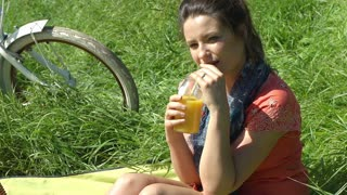 Pretty girl drinking juice while sitting on blanket and smiling to the camera, s