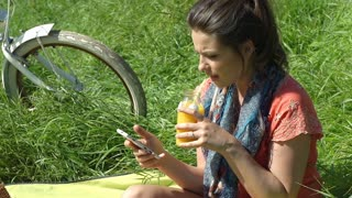 Pretty girl drinking juice while sitting on blanket and texting on smartphone, s