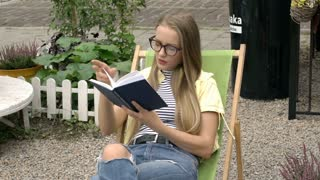 Pretty girl finish reading book on sunbed because of painful headache
