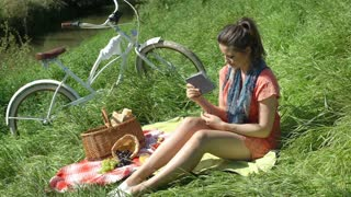 Pretty girl having a picnic and cools herself down with a book, steadycam shot