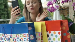 Pretty girl having a videocall and looks dissatisfied while showing her shopping
