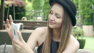 Pretty girl in bowler hat browsing internet on smartphone and smiling to the cam