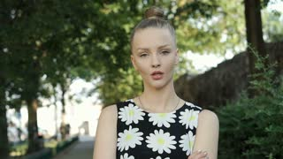 Pretty girl in floral shirt standing in the park and doing angry look to the cam
