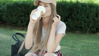Pretty girl in stylish clothes smiling to the camera while drinking coffee in th