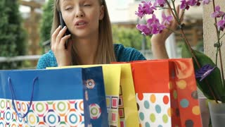 Pretty girl looks dissatisfied while speaking on cellphone and checking her bags