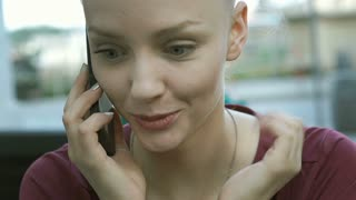 Pretty girl looks excited and surprised while receiving good news on cellphone,