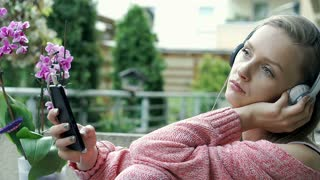 Pretty girl looks sad while listening music on terrace, steadycam shot