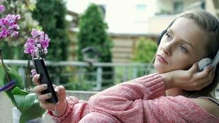 Pretty girl looks sad while listening music on terrace, steadycam shot