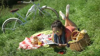 Pretty girl lying on the blanket at sunny day and reading book, steadycam shot