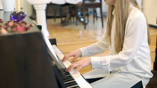 Pretty girl playing the piano and writing music, steadycam shot