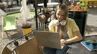 Pretty girl plays music on modern notebook and puts on headphones