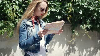 Pretty girl reading map outdoors and smiling to the camera, steadycam shot