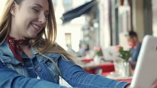 Pretty girl sitting in the outdoor cafe and doing selfies on tablet, steadycam s