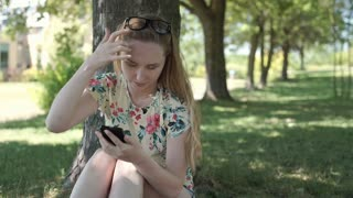 Pretty girl sitting in the park and browsing internet on smartphone, steadycam s