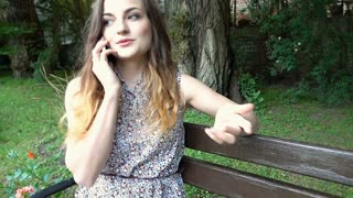 Pretty girl sitting on the bench in the park and chatting on cellphone, steadyca