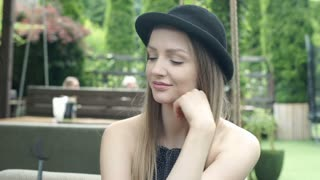 Pretty girl takes off bowler hat and smiling to the camera in the cafe's garden,