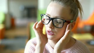 Pretty girl takes off glasses because of painful migraine