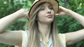Pretty girl takes off straw hat and smiling to the camera, steadycam shot