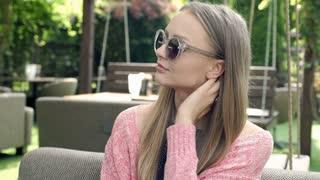 Pretty girl takes off stylish sunglasses and having painful headache, steadycam