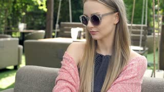 Pretty girl takes off stylish sunglasses and smiling to the camera, steadycam sh