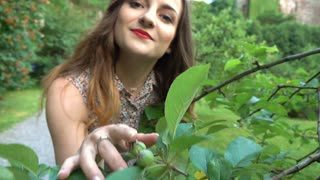 Pretty girl touches tree's brunches and smiling to the camera, steadycam shot, s