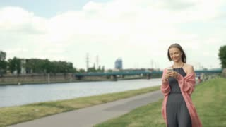 Pretty girl walking on boulevards next to the river and texting on smartphone, s