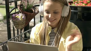 Pretty girl wearing headphones and having a videocall on notebook