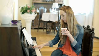 Relaxed girl playing the piano and drinking coffee