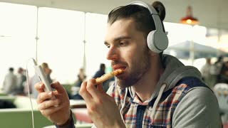 Relaxed man eating pizza while listening music and browsing internet on smartpho