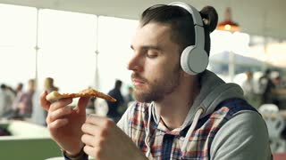 Relaxed man listening music on headphones and eating pizza in bistro, steadycam