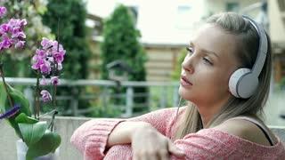 Sad girl sitting on terrace and listening music on headphones, steadycam shot