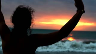 Silhouette of the woman standing on the seaside during sunset and feels free, st