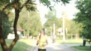 Sporty girl running on pathway in the park and looks tired, steadycam shot