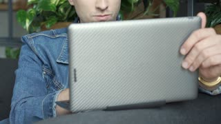 Stylish boy looks absorbed while touching screen on modern notebook, steadycam s