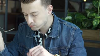 Stylish boy looks unhappy while eating unfresh salad in the cafe, steadycam shot