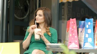 Stylish brunette in green dress drinking frappe and smiling to the camera, stead