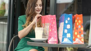 Stylish brunette looks happy while checking her shoppings in the outdoor cafe, s
